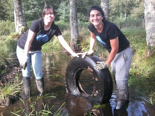 Dos voluntarias sacan un neumático de un río durante la VII Limpieza Simultánea de Ríos en Galicia (foto: Adega).