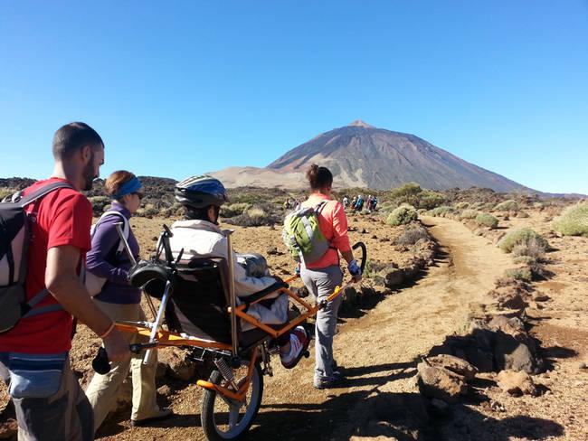 Una persona con movilidad reducida, junto a varios acompañantes, recorre en una joëlette un sendero del Parque Nacional del Teide (foto: FGN).