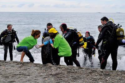 Buceadores y voluntarios extraen un gran neumático en Torre del Mar (Málaga) durante la Gran Limpieza Nacional de Fondos Marinos (foto: Nuria Castaño).