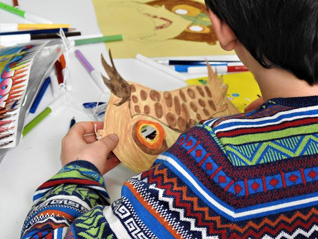 Un niño con una máscara de búho, en un taller de Brinzal en su fiesta de aniversario (foto: Patricia Catalina Allueva).