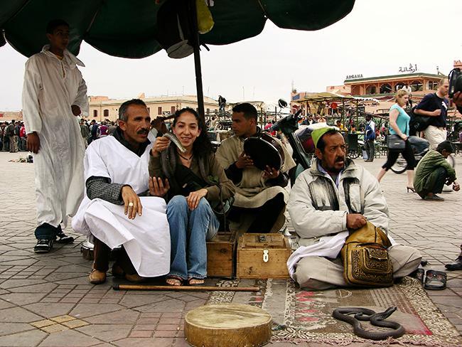Encantadores de serpientes en la plaza Ymaa el Fna de Marrakech posando con una turista (foto: Mónica Feriche).