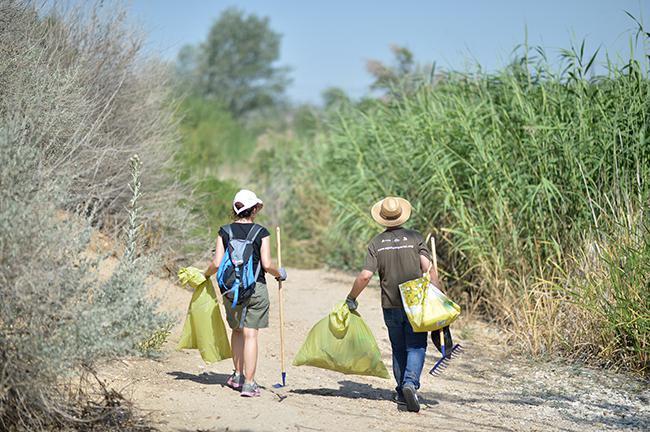 """Dos participantes en la campaña """"1m2 por la naturaleza"""" trasladan la basura que han recogido (foto: Ecoembes)."""