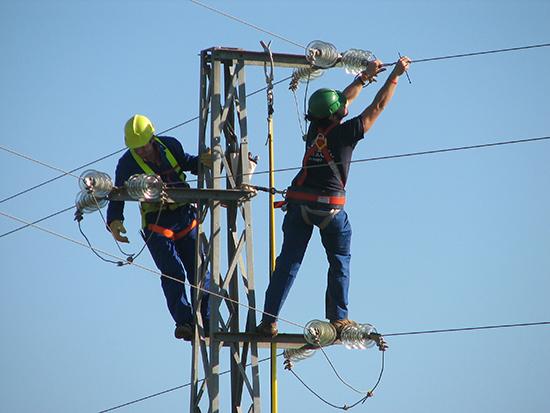 Dos operarios de una compañía eléctrica corrigen un tendido peligroso para las aves (foto: Justo Martín).