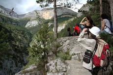 Montaje fotográfico en el que se ve cómo varios participantes en el programa de visitas guiadas del Pirineos Bird Center observan un quebrantahuesos en el Sendero de los Miradores de Revilla (Huesca). Foto: FCQ.
