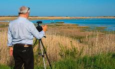 Un hombre graba en vídeo a las aves acuáticas de un humedal (foto: Dimitrina Lavchieva / Shutterstock).