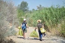 Dos colaboradores del Proyecto Libera trasladan la basura que han recogido en un espacio natural (foto: Ecoembes).