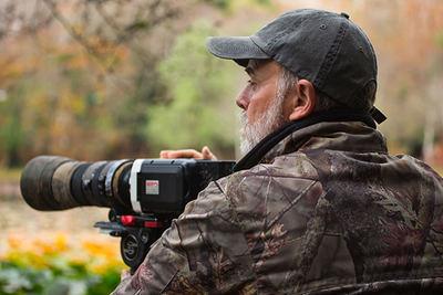 Arturo Menor, cámara en mano durante una jornada de rodaje en el campo.