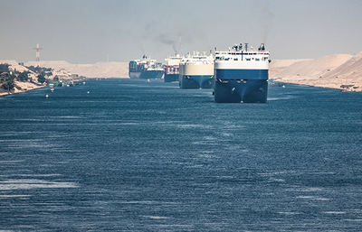 Fila de buques mercantes cruzando el Canal de Suez (foto: Dipix y TommoT / Shutterstock).