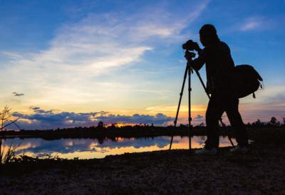 Un fotógrafo de la naturaleza practica su afición junto a un humedal (foto: sabzaa / 123rf).